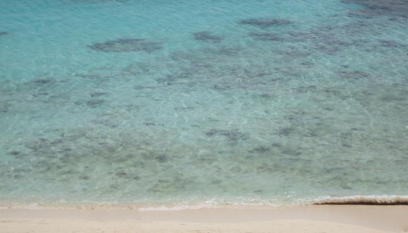 Strand und flaches Wasser mit Korallen